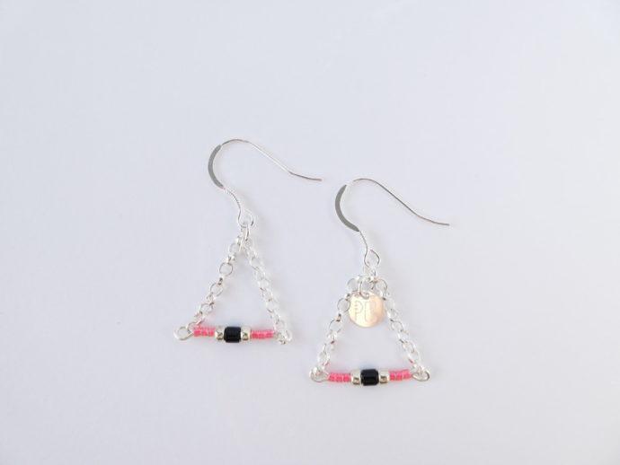 Les boucles d'oreilles roses avec chaîne argent.