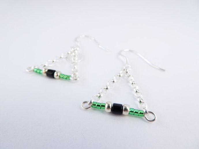 Gros plan sur les perles Miyuki des boucles d'oreilles vertes avec chaîne argent.