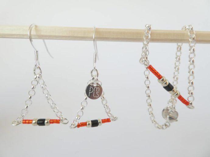 Le bracelet rouge et chaîne argent et les boucles d'oreilles assorties.