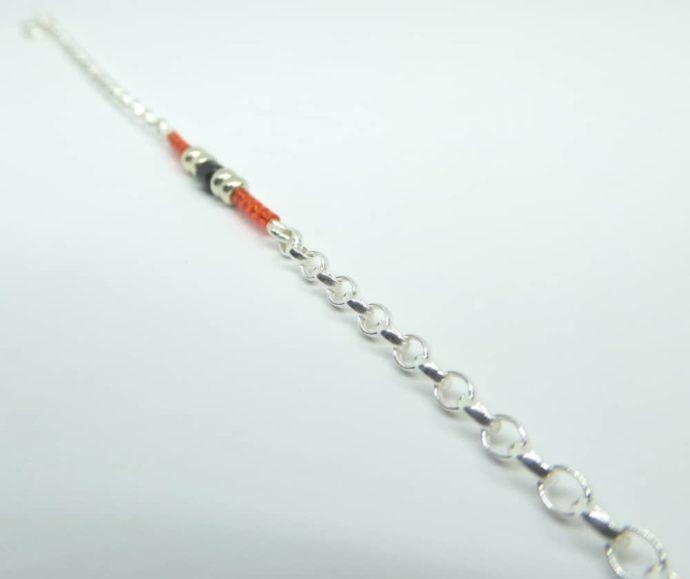 Les mailles Jaseron du bracelet rouge et chaîne argent.