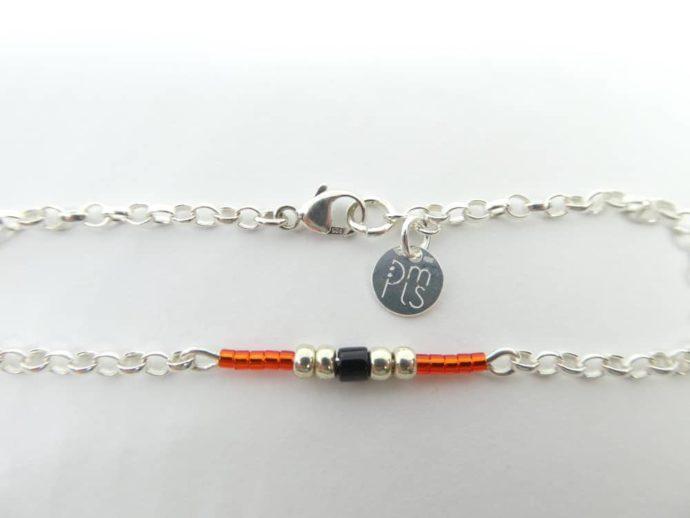 Le fermoir Menotte et la marque PMLS du bracelet rouge avec chaîne argent.