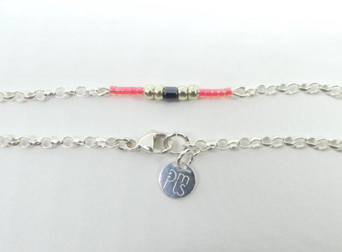 Le fermoir Menotte et la marque PMLS du bracelet rose avec chaîne argent.