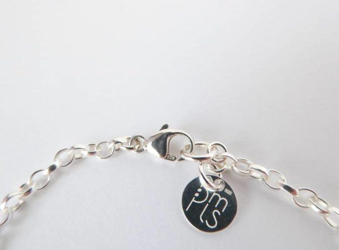Gros plan sur le fermoir Menotte du bracelet vert avec chaîne argent.