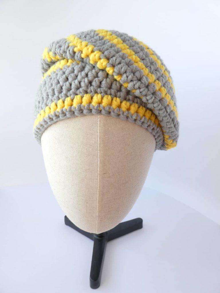 Le bonnet gris et jaune Pantone 2021 porté sur le côté de la tête.