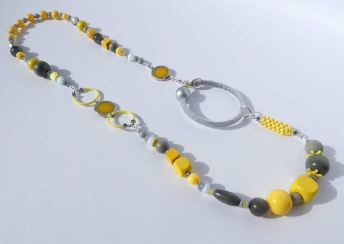 Le collier asymétrique jaune et gris et l'anneau recouvert de velours gris.