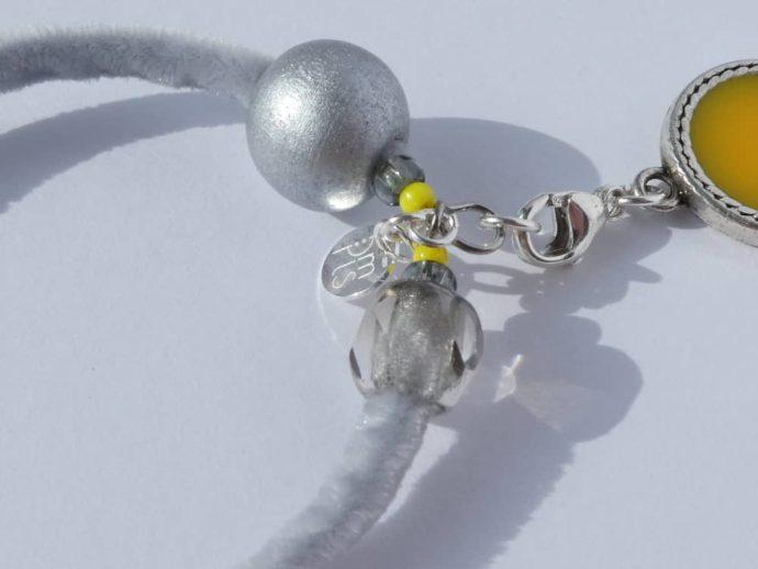 Gros plan sur le fermoir en argent 925 du collier jaune et gris.