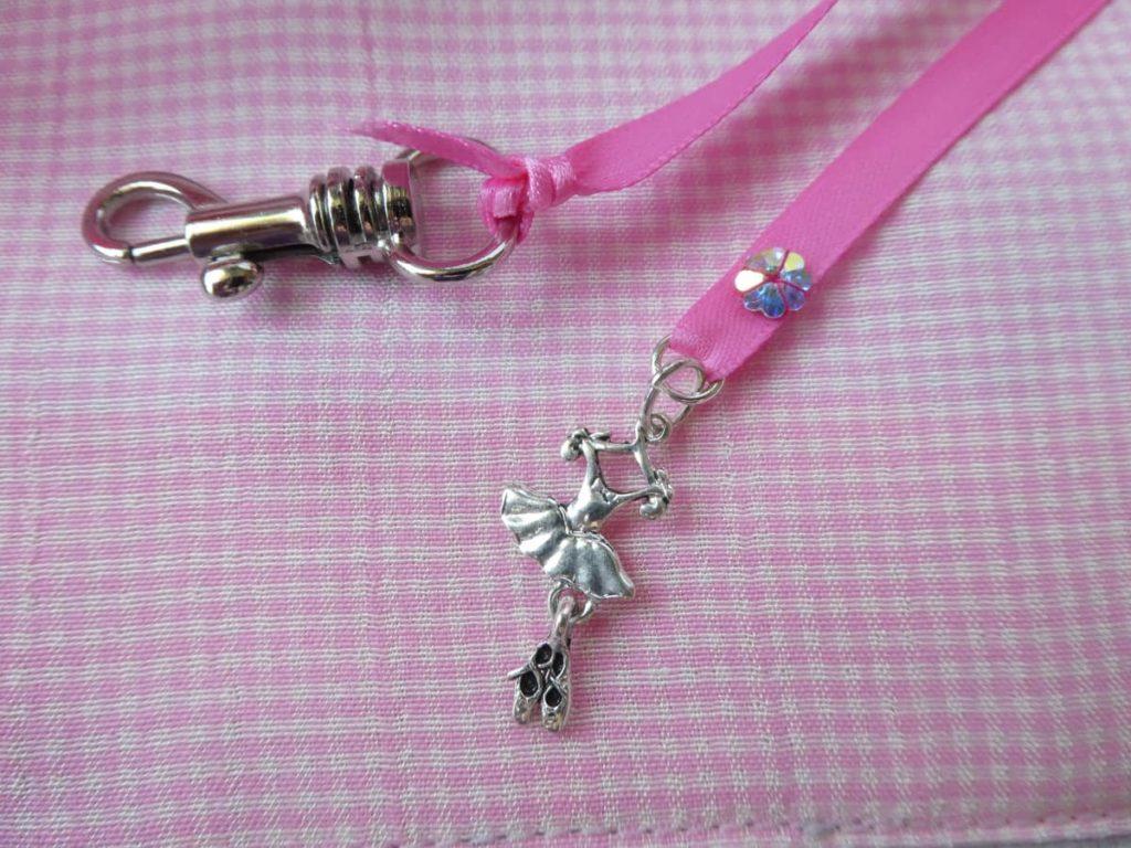 Breloque tutu et mousqueton sur le ruban satin rose.