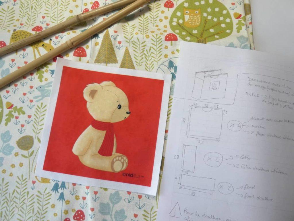 Le tissu imprimé forêt et le tuteur en bambou du sac ourson à l'écharpe rouge.