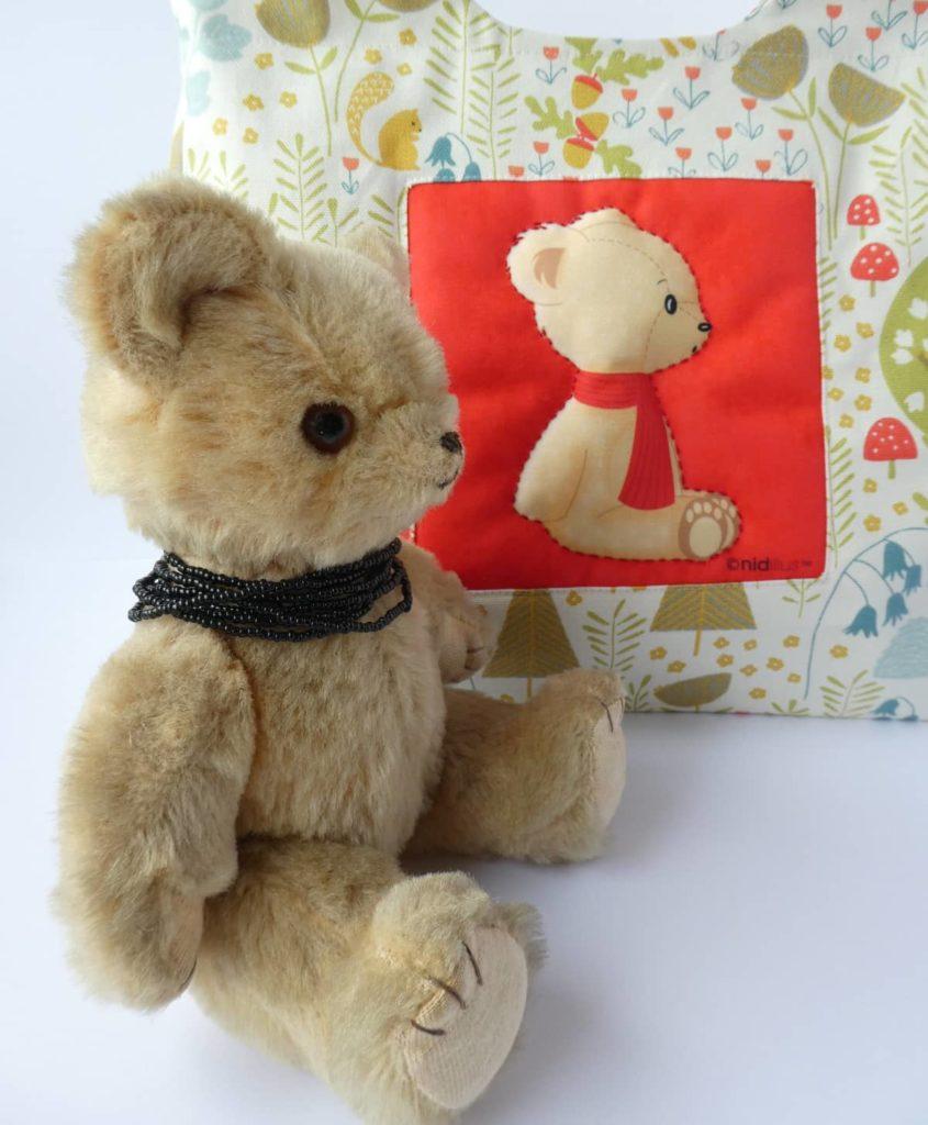 Un nounours et le sac avec le coupon ourson à l'écharpe rouge.