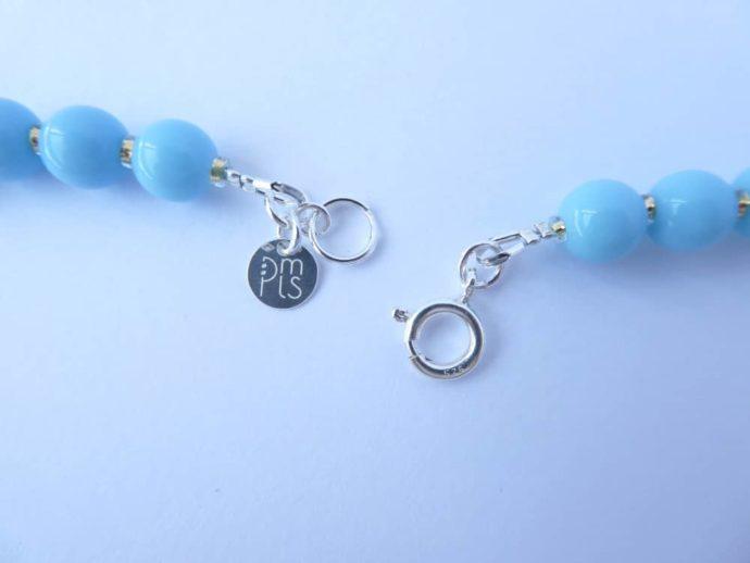 Le fermoir et la marque PMLS du collier bleu Ecalgrain.